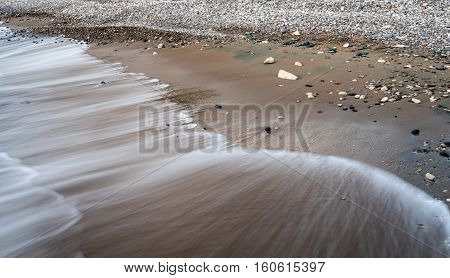 Sea water flowing on a golden beach sand. Long Exposure photography