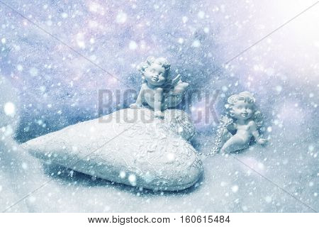 Closeup of beautiful soulful figurine composition of cupid angels for valentine day or christmas with small pillow in shape of heart lying on white wadding decorating snow with purple light sparks