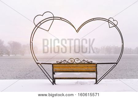 empty snow-covered wrought-iron bench in the form of hearts for couple of lovers in winter park