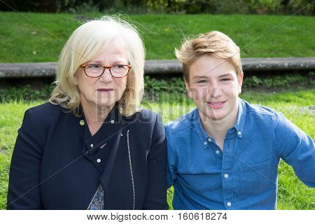 grandchild boy with his gandmother in a park with glasses