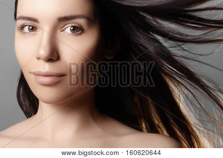 Beautiful young woman model with flying light color hair. Beauty portrait with clean skin glamour fashion makeup. Make up hairstyle. Haircare make-up. Horizontal beauty portrait