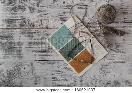handicraft and needlework concept - knitting needles and balls of yarn on wood poster