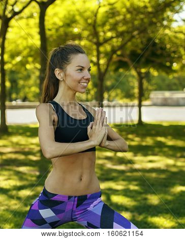 Portrait of beautiful caucasian girl doing yoga outdoors on nature background holding hands in namaste. Harmony healthy lifestyle.