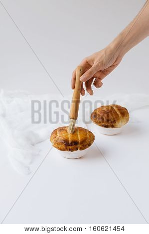 Male Hand Brushing top of Pie with Milk on White Table