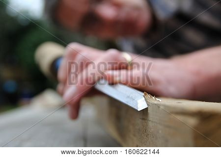 Traditional Woodworker Using Wooden Mallet And Chisel