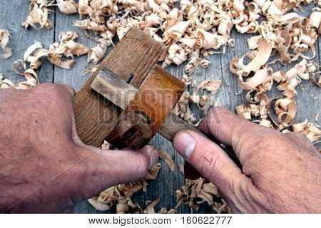 Traditional woodworker using antique wooden mortise gauge poster