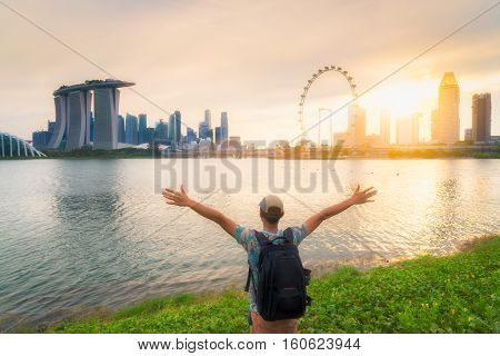 Man standing with open free arm and enjoy the beautiful sunrise time at Singapore - Success concept.