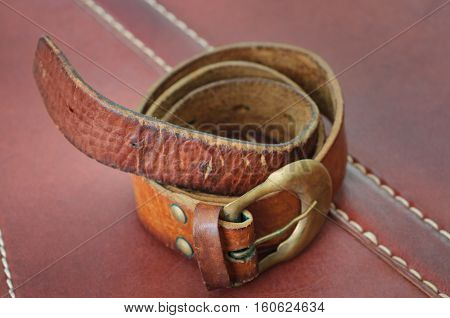 old brown belt on a brown background of skin