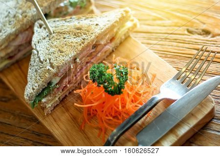 Club sandwich on the wood plate decorate with chopped carrot and parsley together with fork and knight on the bark wood table background
