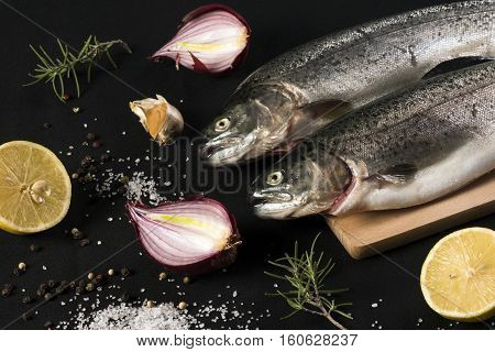 Raw trout fish with salt pepper lemon garlic onion and rosemary on black background.