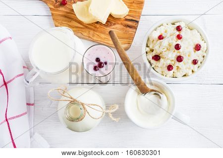 Dairy produce. Milk in bottle cottage cheese in bowl kefir in jar cranberry yogurt in glass butter and fresh berries. Wooden white table top view.