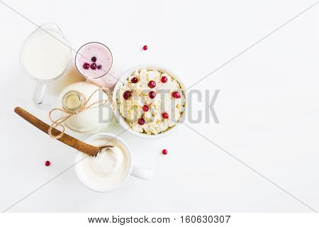 Dairy produce. Milk in bottle cottage cheese in bowl kefir in jar cranberry yogurt in glass butter and fresh berries. White table top view.
