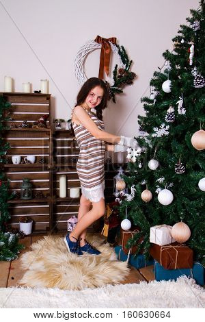 Happy and contented little girl dresses up Christmas tree