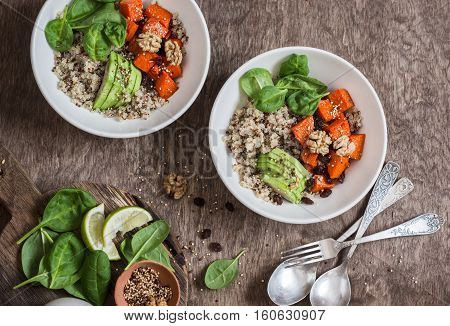 Quinoa and pumpkin bowl. Vegetarian healthy diet food concept. On a wooden table top view. Flat lay