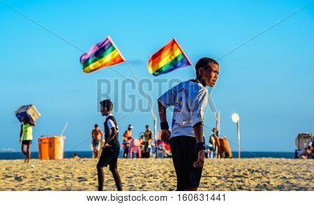 December 06, 2016. Brazilian boys playing football at Copacabana beach on the background of two rainbow flags, Rio de Janeiro, Brazil