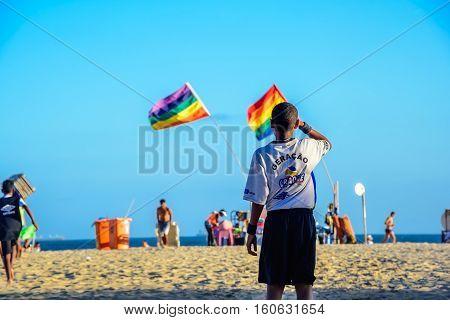 December 06, 2016. Backs of brazilian boys playing football at Copacabana beach on the background of two rainbow flags, Rio de Janeiro, Brazil