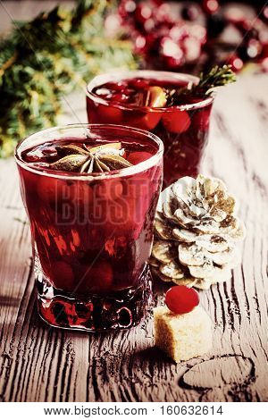 Christmas decoration and mulled wine with cranberries anise and oranges. Dark wooden background vintage effect toned image.