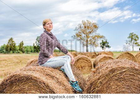 Young woman sitting on hay roll bale