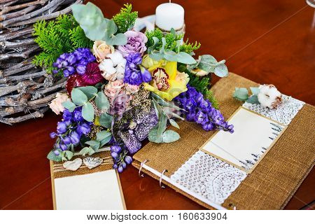 Close up of wedding photo book album bouquet eucalyptus cotton and other violet pink yellow flowers.