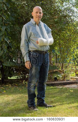 Young Man With An Arm Cast Standing In The Garden