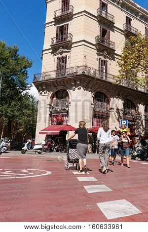 BARCELONA, SPAIN - SEPTEMBER 19, 2016; People cross city street women with pushchairs walk away while young family walk other way on Carrer De LA Princesa Barcelona Spain