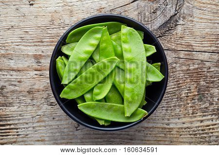 Bowl Of Snow Peas On Wooden Table, From Above