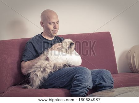 Young Man With An Arm Cast Petting His Cat