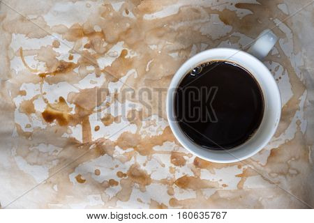 cup of coffee on worn paper with coffee stains and rough