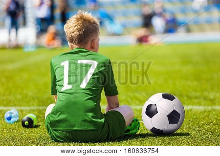 Young Soccer Football Player. Little Boy Sitting on Soccer Pitch. Youth Football Player in Green Soccer Jersey