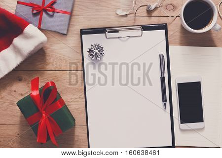 Christmas planning background. Prepare to winter holidays. Top view flat lay of xmas decorations and present, note papers, pen, coffee and mobile phone on wood. Copy space for wishlist or schedule
