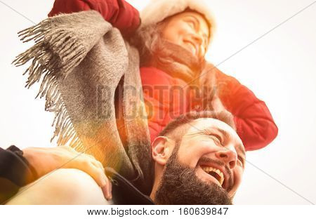 Happy couple of travelers in love enjoying winter time outdoor - Handsome hipster man with young woman on piggyback balance - Relationship concept with boyfriend and girlfriend on warm sunshine filter