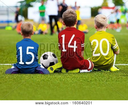Children Soccer Team Playing Match. Football Game for Kids. Young Soccer Players Sitting on Pitch. Little Kids in Colorful Soccer Jersey Sportswear