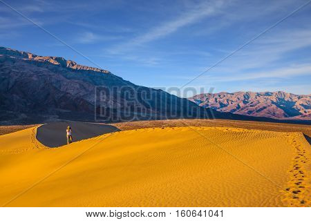 Woman in striped shirt photographing sand waves. Mesquite Flat Sand Dunes. Bright sunny morning in a picturesque part of Death Valley, USA