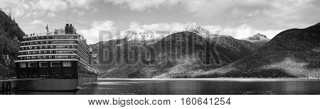 The panoramic view of a mountain range and a cruise liner docked in Skagway town (Alaska).