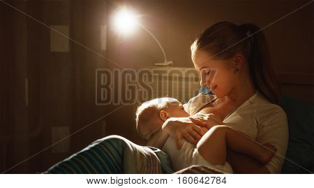 breastfeeding. mother feeding a baby breast in bed dark night poster