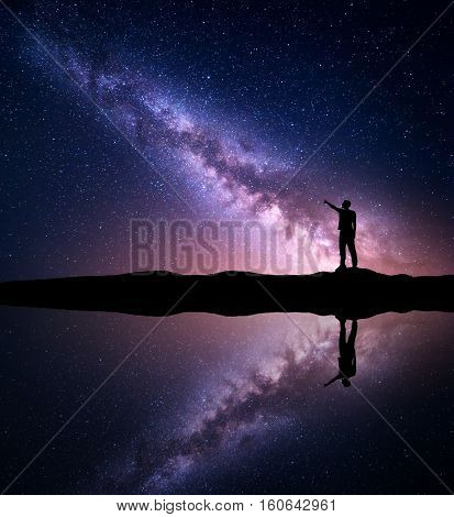 Milky Way. Silhouette of a standing man pointing finger in night starry sky on the mountain near the river with sky reflection in water. Night landscape with galaxy. Purple milky way and man. Universe