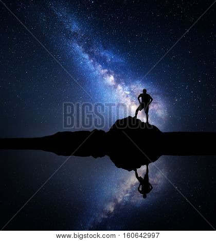 Milky Way. Night starry sky and silhouette of a standing man with backpack on the stone near the lake with sky reflection in water. Milky way and man on the mountain. Galaxy and silhouette of a man