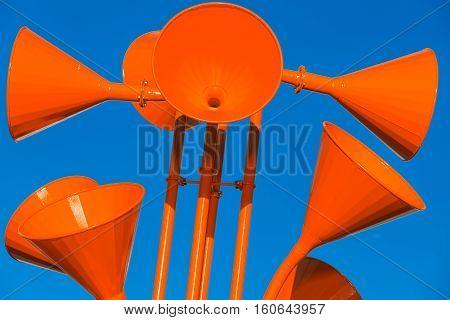 Red Loudspeakers Over Blue Sky