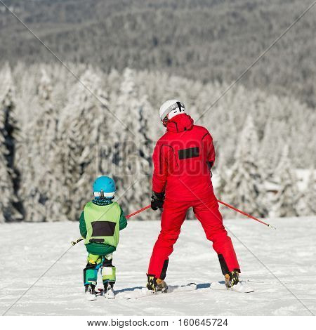 Father and son slowly skiing together. Father and son skiing together