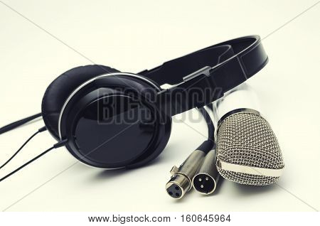 White microphone and headphones black on a light background