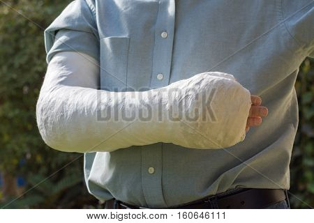 An arm and elbow in a white plaster / fiberglass cast worn by a young man standing in a garden poster