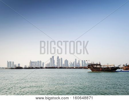 doha city skyscrapers urban skyline view and dhow boat in qatar