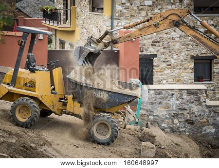 construction works with an excavator and a mini dumper truck
