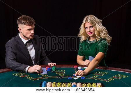 couple playing poker at the table. The blonde girl and a guy in a suit. Woman bets chips