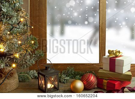 Christmas tree gifts and decorations next to a window with snow scenery outdoors