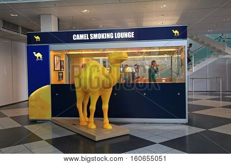MUNICH, GERMANY - JULY 25, 2016: Camel Smoking lounge with passengers inside in Munich International Airport, Germany. Smoking lounge is only zone where people can smoke inside airport building. Camel is sponsor of all smoking areas in german airports