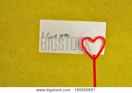 Valentines day. A note holder with a red heart with a note reading i love you isolated against a yellow background