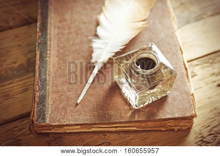 Feather pen with inkwell and old book on wooden table closeup