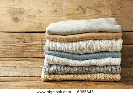 Stack of folded clothes on wooden background