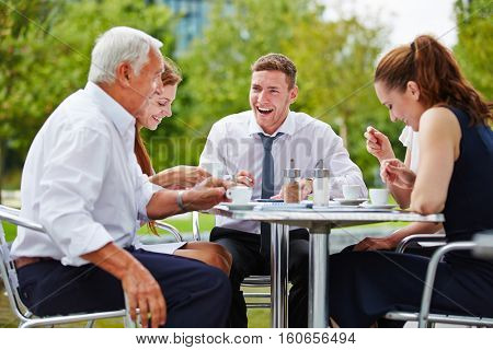 Business people drinking coffee and talking during their break